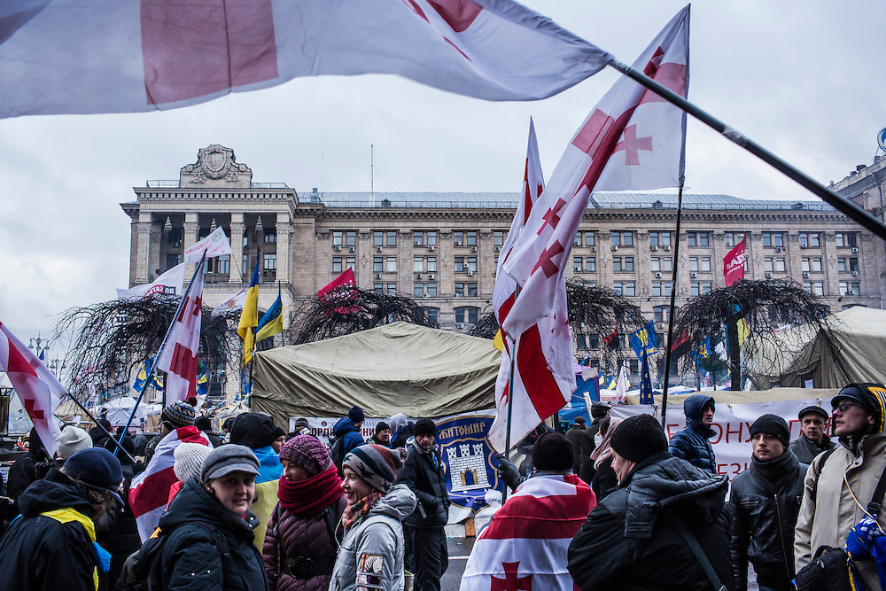 KIEV, UKRAINE - DECEMBER 7: Anti-government protesters hold Georgian flags in anticipation of an appearance by former Georgian president Mikheil Saakashvili on Independence Square on December 7, 2013 in Kiev, Ukraine. Thousands of people have been protesting against the government since a decision by Ukrainian president Viktor Yanukovych to suspend a trade and partnership agreement with the European Union in favor of incentives from Russia. (Photo by Brendan Hoffman/Getty Images) *** Local Caption ***