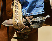 The boots, spurs, and chaps are functional pieces of equipment used every day by the American cowboy. As well as being functional they can be quite decorative and the spurs are often inlayed with silver or gold. This cowboy proudly wears silver inlayed trophy spurs he won as a team roper.