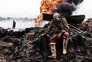Iraq, Qayyara: An Iraqi firefighter takes a break while his colleagues try to extinguish oil wells put on fire by ISIS members as they were retreating. Alessio Romenzi