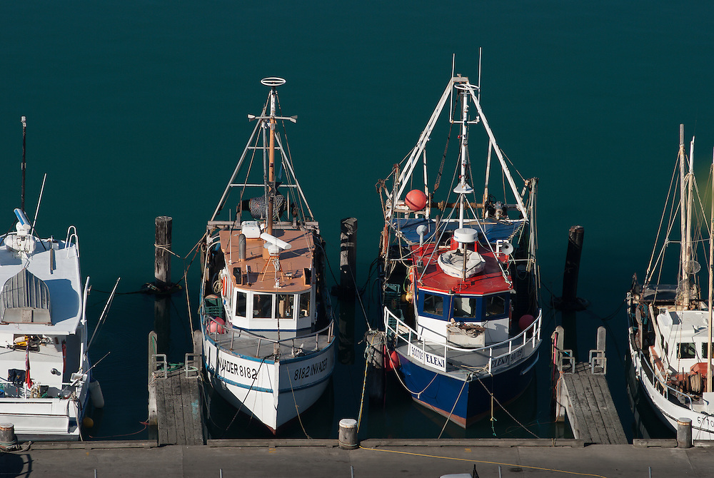 Two small fishing boats moored at Lyttelton, New Zealand surrounded by teal green harbour water