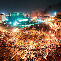 Demonstrators gather in Tahrir Square during clashes with riot police as the National Democratic Party headquarters (background) burns in downtown Cairo, Egypt. January 2011.