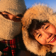 A holiday couple from Singapore cuddle together on the cold Austrian ski slopes in Salzburg.