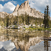 The pyramidal peak of El Capitan (9846 feet or 3001 elevation) reflects in the outlet stream of Alice Lake (Pettit Lake Creek) in Sawtooth Wilderness, Blaine County, Idaho, USA. The Sawtooth Range (part of the Rocky Mountains) are made of pink granite of the 50 million year old Sawtooth batholith. Sawtooth Wilderness, managed by the US Forest Service within Sawtooth National Recreation Area, has some of the best air quality in the lower 48 states (says the US EPA). Panorama stitched from 2 overlapping photos.