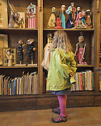 Young girl studies the puppets and books