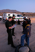 U.S. Border Patrol Agent Thomas Steele (left) processes five illegal aliens he apprehended in the desert near El Centro, Calif. on Wednesday, March 30, 2005.<br />