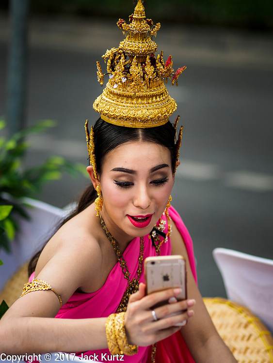 "08 APRIL 2017 - BANGKOK, THAILAND: An entertainer uses an iPhone for a video chat before the ""Amazing Songkran"" festival in Benchasiri Park in Bangkok. The festival was sponsored by the Tourism Authority of Thailand to highlight the cultural aspects of Songkran. Songkran is celebrated in Thailand as the traditional New Year's Day from 13 to 16 April. Songkran is in the hottest time of the year in Thailand, at the end of the dry season and provides an excuse for people to cool off in friendly water fights that take place throughout the country. Songkran has been a national holiday since 1940, when Thailand moved the first day of the year to January 1. Songkran 2017 is expected to be more subdued than Songkran usually is because Thais are still mourning the October 2016 death of revered King Bhumibol Adulyadej.       PHOTO BY JACK KURTZ"