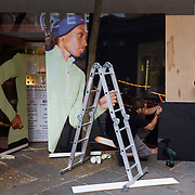 A building worker bends and attends to a panel while converting a high-street shop in London's Covent Garden.
