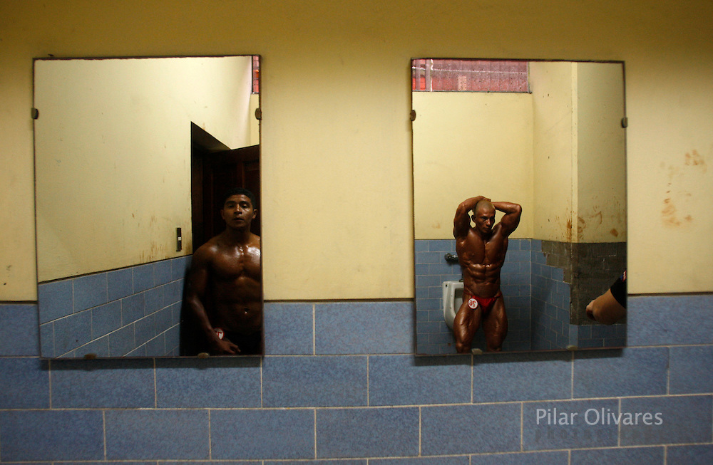 Competitors, reflected in mirrors, wait for their turn in a bodybuilding competition in Lima January 30, 2010.