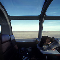 Canada, Alberta, (MR) Chris Wrenn naps in dome car of VIA Rail passenger train traveling through Saskatchewan