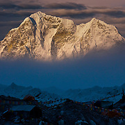 Sunset and cloud paint the landscape outside of Everest Basecamp, Nepal. The visible peak in the distance is Tawoche.