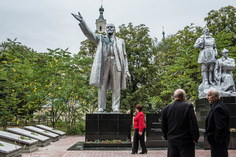 SEMYONOVKA, UKRAINE - SEPTEMBER 13, 2015: Tatyana I. Pus, 68, Ivan Kovalenko, 69, and Ivan M. Papchenko, 67, the secretary of the local Communist party, from left, near a reconstituted statue of Vladimir I. Lenin in Semyonovka, Ukraine. The statue, which was taken down from the town square in the immediate aftermath of the collapse of the government of President Viktor Yanukovych in February 2014, was erected again in a new, more discreet, location in a park two months later based in part by a petition to the city council submitted by the local Communist party. A new decommunization law has stirred criticism as being a diversion from more pressing issues of war and the economy. CREDIT: Brendan Hoffman for The New York Times