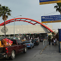 Cars wait to cross into Matamoros, Mexico, that borders town Brownsville, TX, on April 23, 2010. The region is a conduit for drugs moving north into the US and drug proceeds and weapons moving south from Texas into Mexico. (Photo/Scott Dalton)