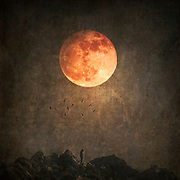 Photomanipulation with my own images - surreal mountain landscape with solitary figure and full moon