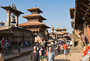 """Visitors stroll in Patan's Durbar Square, in Nepal, Asia. Patan was probably founded by King Veer Deva in 299 AD from a much older settlement. Patan, officially called Lalitpur, the oldest city in the Kathmandu Valley, is separated from Kathmandu and Bhaktapur by rivers. Patan (population 190,000 in 2006) is the fourth largest city of Nepal, after Kathmandu, Biratnagar and Pokhara. The Newar people, the earliest known natives of the Kathmandu Valley, call Patan by the name """"Yala""""  (from King Yalamber) in their Nepal Bhasa language. UNESCO honored Patan's Durbar Square (Palace Square) as one of the seven monument zones of Kathmandu Valley on their World Heritage List in 1979. All sites are protected under Nepal's Monuments Preservation Act of 1956. Published in """"Light Travel: Photography on the Go"""" book by Tom Dempsey 2009, 2010."""