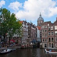 Amsterdam, Holland. Canal scene with St. Nicholas Church behind the traditional houses.