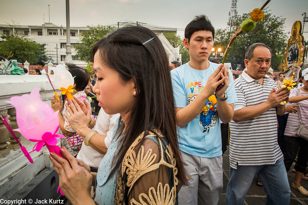 """25 FEBRUARY 2013 - BANGKOK, THAILAND:   Thai Buddhists pray at Wat Benchamabophit Dusitvanaram (popularly known as either Wat Bencha or the Marble Temple) on Makha Bucha Day. Makha Bucha is a Buddhist holiday celebrated in Myanmar (Burma), Thailand, Cambodia and Laos on the full moon day of the third lunar month (February 25 in 2013). The third lunar month is known in Thai is Makha. Bucha is a Thai word meaning """"to venerate"""" or """"to honor"""". Makha Bucha Day is for the veneration of Buddha and his teachings on the full moon day of the third lunar month. Makha Bucha Day marks the day that 1,250 Arahata spontaneously came to see the Buddha. The Buddha in turn laid down the principles his teachings. In Thailand, this teaching has been dubbed the 'Heart of Buddhism'.    PHOTO BY JACK KURTZ"""