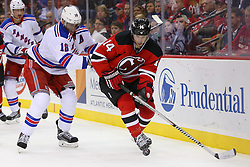 Oct 21, 2014; Newark, NJ, USA; New Jersey Devils center Adam Henrique (14) skates with the puck while being defended by New York Rangers defenseman Marc Staal (18) during the second period at Prudential Center.