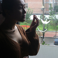 """BEJING,CHINA-SEPTEMBER 4: Lucy,Hao,24,a jewlery trader,stands near a window  in a cafe with her """"new face"""" and """"new breasts"""", on September 4 ,2003,in Beijing,China. While waiting for the next surgery on September 8,2003 where she'll have lipsucction on her tights,Hao keeps herself busy with shoppping and """"taking care of herself"""". ..Hao sparked a  media frenzy when she announced some weeks ago that  she'll undergo  cosmetic surgery 14 times in order to enhance her  nose,hairline,eyes,jaws,neck,bottom,breats and legs.Hao believes being""""pretty"""" is essential in China's society to be successful ,in her case she plans to become an actress.Cosmetic clinics have poppped up all over urban China as western features have  become very popular with urban Chinese women who want to distinguish themseleves from the masses and the majority of whom is between 20-30 year old .  Hao's surgery costs USD 50,000 and reportedly is the most expensicve cosmetic surgery in China up to now..."""