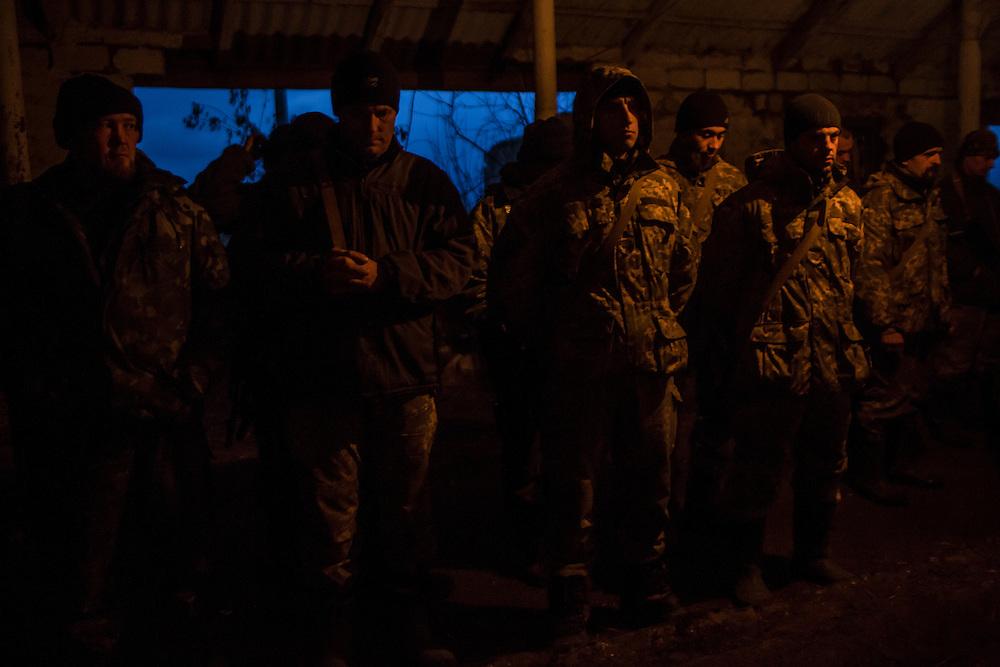 Ukrainian soldiers line up for the evening roll call and prayer at an artillery depot on Monday, December 14, 2015 near Slovyansk, Ukraine.