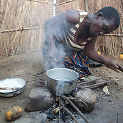 "7 June 2010, Mbiya Camp, Mazabuka, Zambia. Catherine Kandundu prepares a porridge made from ground maize or ""nchima"", the staple food of Zambians."