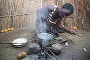 "7 June 2010, Mbiya Camp, Mazabuka, Zambia. Catherine Kandundu prepares a porridge made from ground maize or ""nchima"", the staple food of Zambians."