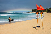 A low rainbow shines over a surfer at Ehukai Beach Park; orange flags and signs warn of strong current and no swimming. The famous Banzai Pipeline surf reef break is offshore from Ehukai Beach Park in Pupukea on the North Shore of the island of Oahu, Hawaii, USA. Especially in winter, huge series of waves break into tubes upon reaching the shallows of the reef. This popular area, across the street from Sunset Beach Elementary School, has limited parking. Hawaii was first settled by Polynesians in several waves from about 300-1000 AD. Although surfing was first described in writing by Europeans visiting Hawaii in 1769 and 1779, the riding of waves with a wooden board likely originated in Western Polynesia thousands of years earlier. Hawaii is 2300 miles distant from the North American continent and is the northernmost island group in Polynesia.
