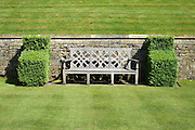 A Medieval style timber seat flanked by buttresses of clipped box (Buxus sempervirens) against a Cotswold stone wall in an English country garden.<br />