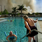 Pat Miele, of Plaistow, NH, left, relaxes in the pool of the Theme World  RV Park while talking with friend Joyce Franklin, of Binghanton, NY, right, as muck fire burns nearby on Tuesday, March 3, 2001 in Davenport, Fla.(AP Photo/Scott Audette)