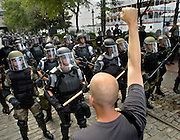 A G-8 protestor stands in defiance of the riot police during a march through the streets of Savannah, Ga.