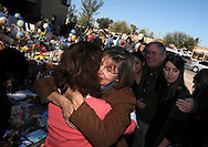 Employee, Pam Simon, (center), a survivor of the shooting spree during an attempt to assassinate Arizona congresswoman, Gabrielle Giffords, on Jan. 8, 2011, returns to Giffords' office after her release from the hospital.  She is greeted by friends at the large memorial created at Giffords office.