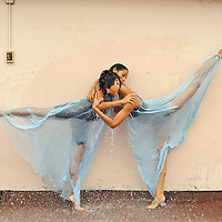 MR. Model relased photo. Dancers hugging and wearing a blue dress soaked by pouring water.