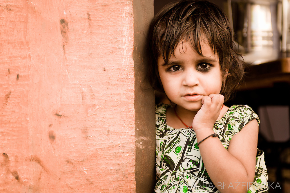 India, Jodhpur. A little shy girl at the door of her house.