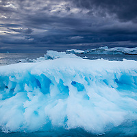 Greenland, Ilulissat, Melting iceberg floating near face of Jakobshavn Isfjord on stormy evening