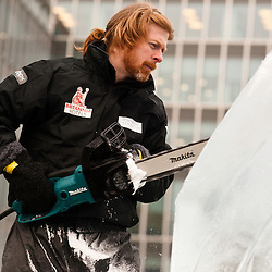 London, UK - 11 January 2012: Niall Magee carves a block of ice during the Ice sculpting festival 2013 in Canary Warf.