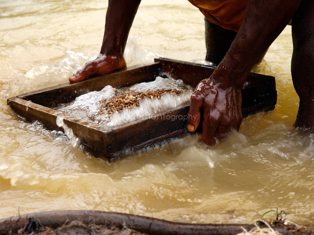A miner sifting gravel to find diamonds and gold, Manamu, Kingsville, Liberia.