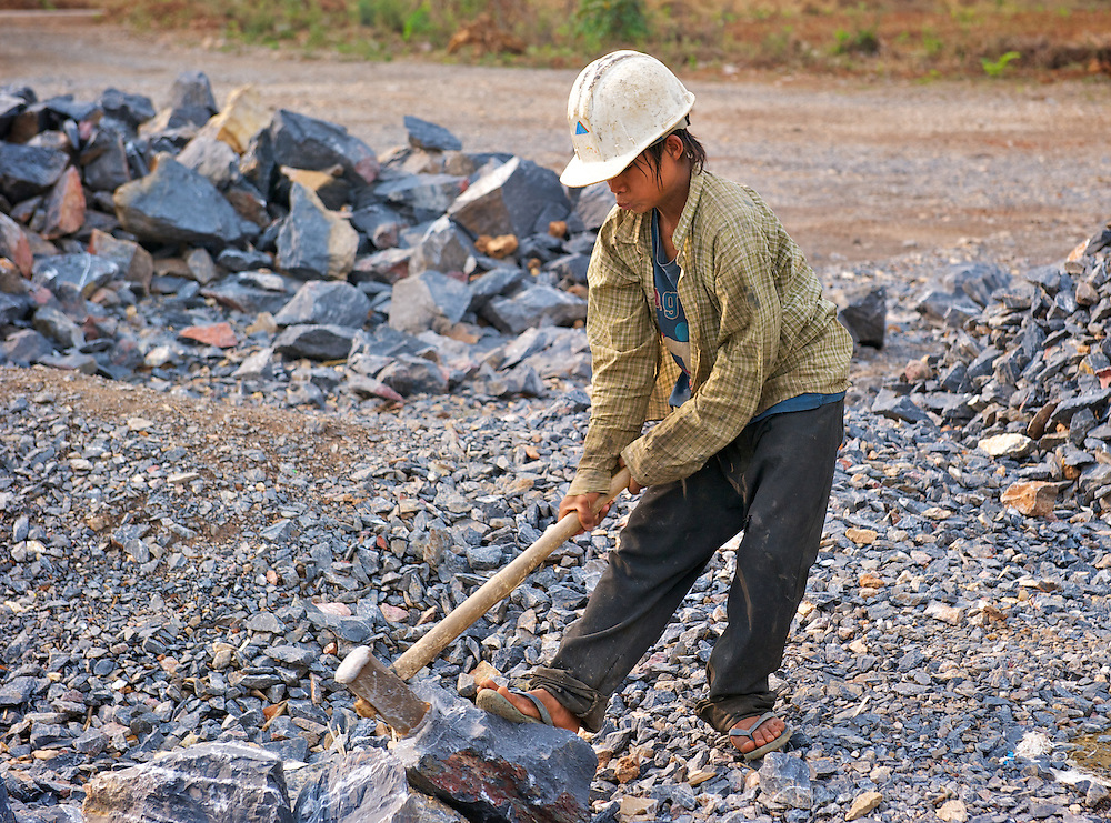 A boy uses a large hammer to break stones in small pieces to be used for road construction