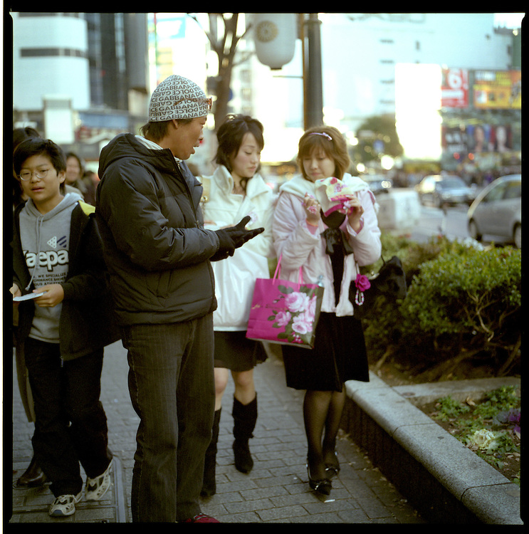 Nowhere to escape.  Young women try to evade gal-O recruiter for modeling agency or hostess bar, Shibuya, Tokyo, Japan