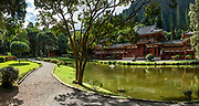 """The peaceful Byodo-In Temple reflects in a koi pond in Valley of the Temples Memorial Park, at 47-200 Kahekili Highway, Kaneohe, on the island of Oahu, Hawaii, USA. The Byodo-In Temple (""""Temple of Equality"""") was built in 1968 to commemorate the 100 year anniversary of the first Japanese immigrants to Hawaii. This Hawaii State Landmark is a non-practicing Buddhist temple which welcomes people of all faiths. The beautiful grounds at the foot of the Ko'olau Mountains include a large reflecting pond stocked with Japanese koi carp, meditation niches, and small waterfalls. Byodo-In Temple in O'ahu is a half-scale replica of the original Byodo-in Temple built in 1053 in Uji, Japan (a UNESCO World Heritage Site). This image was stitched from multiple overlapping images."""