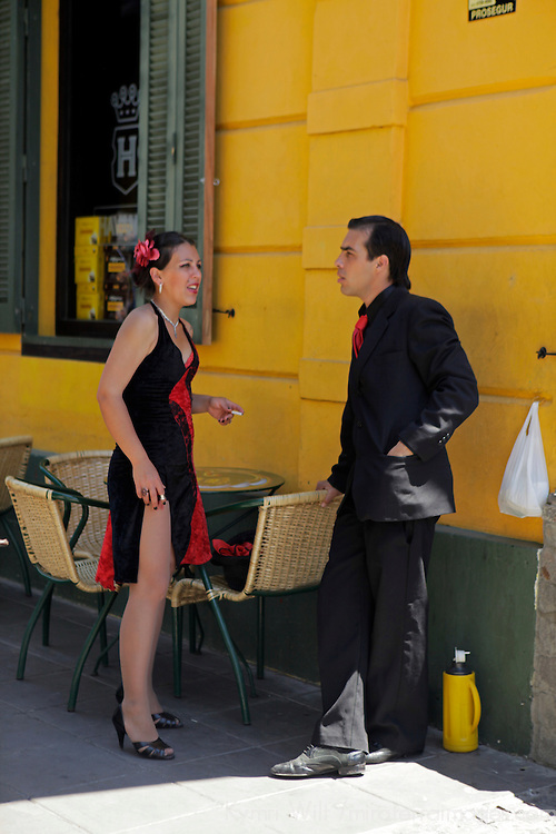 South America, Argentina, Buenos Aires. Tango dancers rest in shade in la Boca.