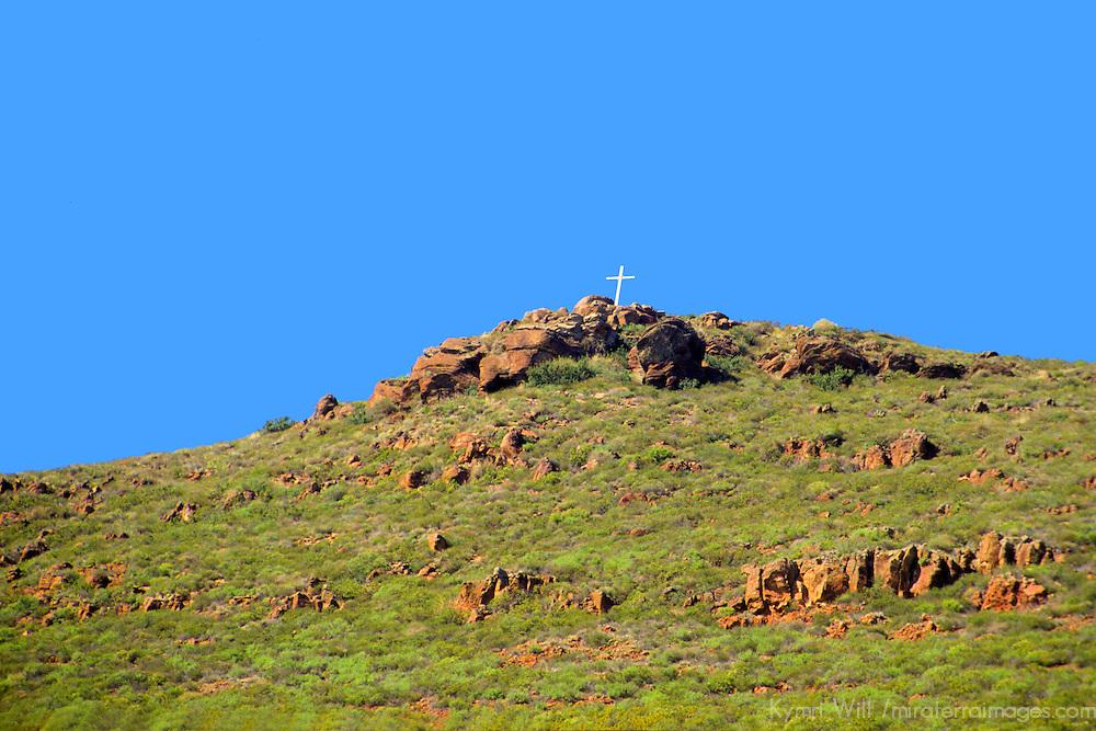 North America, Mexico, Baja California, Ensenada.  A lone cross tops a hill among the MX-1 in Baja California.