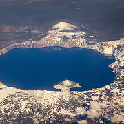 The deep blue color of Crater Lake is visible in this early spring aerial view over Crater Lake National Park, Oregon. Crater Lake, located in the caldera of what was once Oregon's Mount Mazama, is the deepest lake in the United States and the seventh deepest in the world. Its deep blue color results from the clarity of the water. The water is so clear that sunlight travels deep into the lake, losing all but the blue wavelengths in the process. Crater Lake has a maximum depth of 1,946 feet (593 meters). Wizard Island, a volcanic cinder cone that rises about 755 feet (230 meters) above the lake, is visible at the bottom-center of the lake in this image.