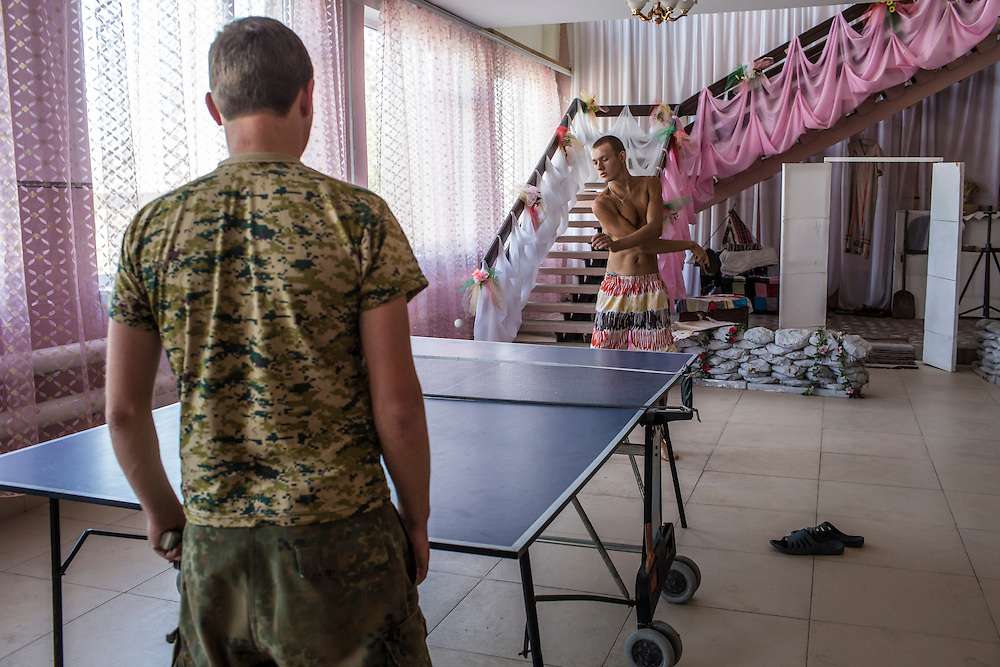 CHERMALYK, UKRAINE - AUGUST 29, 2015: Yan Mishin, 18, plays ping pong with a Ukrainian soldier, left, at the former house of culture, which has been repurposed as a barracks for soldiers, in Chermalyk, Ukraine. The village is located along the west bank of the Kalmius River, which serves as the de facto border between Ukrainian-held territory and that held by pro-Russian rebels. Two days earlier, shelling damaged a local farm. CREDIT: Brendan Hoffman for The New York Times