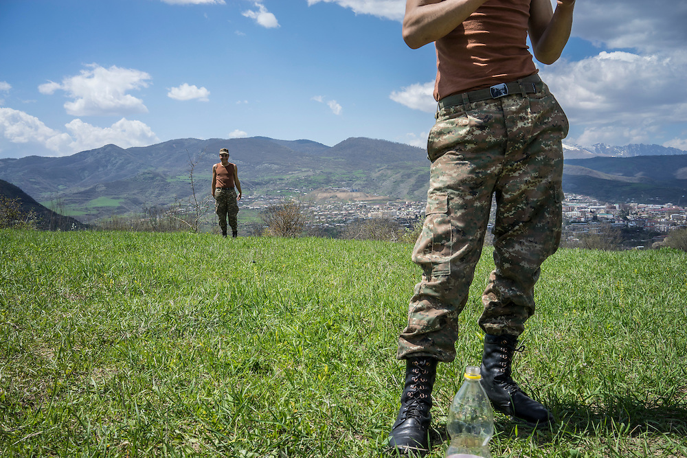 KARASHEN, NAGORNO-KARABAKH - APRIL 19: Samson Israelyan (L), a 20-year-old Armenian soldier from Spitak, on a hill overlooking Stepanakert on April 19, 2015 in Karashen, Nagorno-Karabakh. Since signing a ceasefire in a war with Azerbaijan in 1994, Nagorno-Karabakh, officially part of Azerbaijan, has functioned as a self-declared independent republic and de facto part of Armenia, with hostilities along the line of contact between Nagorno-Karabakh and Azerbaijan occasionally flaring up and causing casualties. (Photo by Brendan Hoffman/Getty Images) *** Local Caption ***