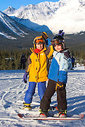 Alaska. Girdwood. Alyeska Resort. Two young snowboarders enjoy the sunshine and excellent snow conditions at Alaska's premiere resort destination.
