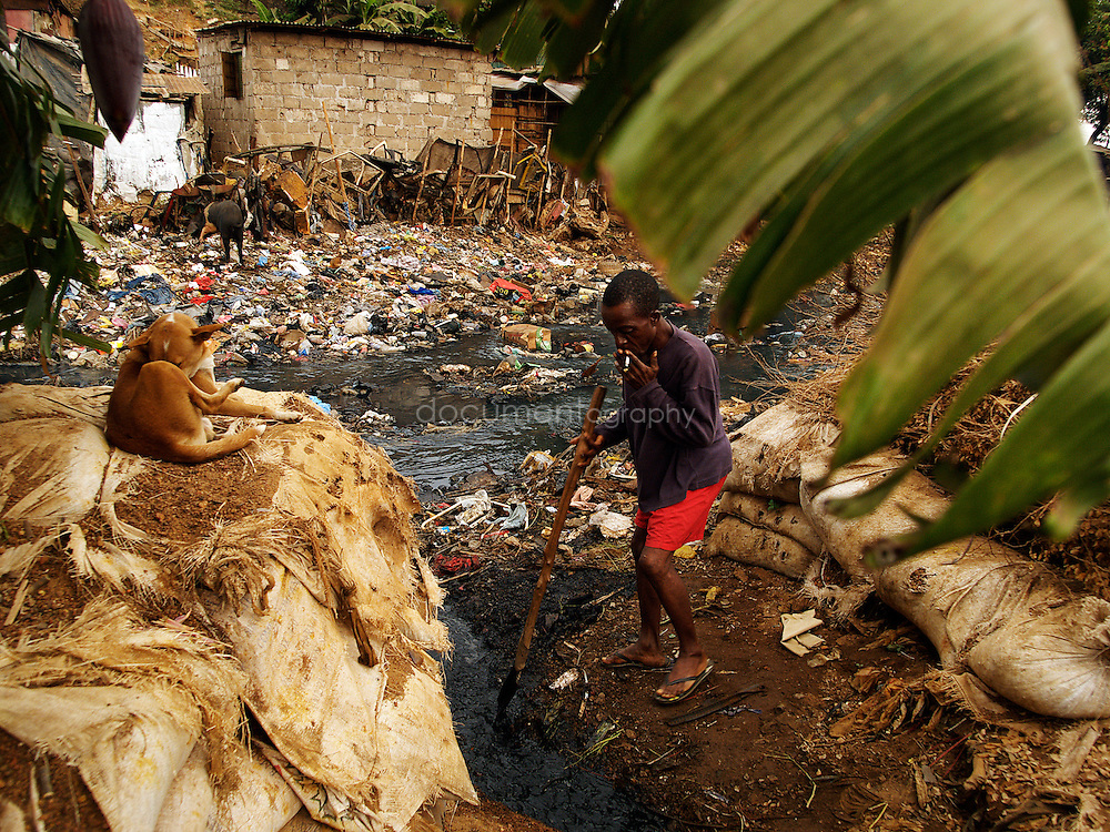 Every morning, Sunkari's husband cleans the open drain at the back of their house, Kroo Bay, Freetown, Sierra Leone.