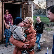"""12 of April 2015 / Petrovski/ Donetsk Oblast/ Ukraine - Tomas Vlach (on the right) emergency coordinator for the NGO """"People in Need"""" welcome by some members of families living in the bunker."""