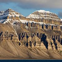 Norway, Svalbard, Spitsbergen Island, Setting midnight sun lights eroded cliffs and mountain peaks in Billefjorden along Isfjorden