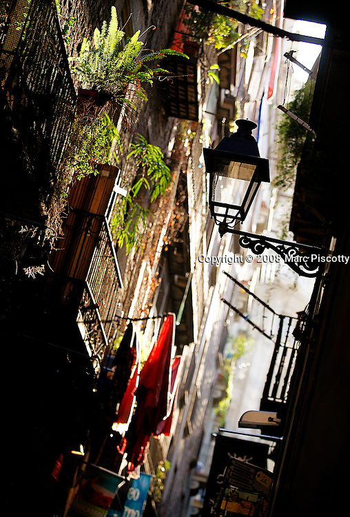 SHOT 11/7/09 8:54:37 AM - Late afternoon sunlight filters into an alley in the Gothic Quarter of Barcelona, Spain. Barcelona is the capital and the most populous city of the Autonomous Community of Catalonia and the second largest city in Spain, with a population of 1,615,908 in 2008. It is located on the Mediterranean coast between the mouths of the rivers Llobregat and Besòs and is bounded to the west by the Serra de Collserola ridge. Barcelona is recognized as a global city because of its importance in finance, commerce, media, entertainment, arts and international trade. Barcelona is a major economic centre with one of Europe's principal Mediterranean ports, and Barcelona International Airport is the second largest in Spain. Barcelona is today an important cultural centre and a major tourist destination and has a rich cultural heritage. Particularly renowned are architectural works of Antoni Gaudí and Lluís Domènech i Montaner that have been designated UNESCO World Heritage Sites. The city is well known in recent times for the 1992 Summer Olympics. Includes images of the El Gòtic, also known as Barri Gòtic ('Gothic Quarter' in Catalan; Spanish: Barrio Gótico) is the centre of the old city of Barcelona. The Barri Gòtic retains a labyrinthine street plan, with many small streets opening out into squares. Most of the quarter is closed to regular traffic although open to service vehicles and taxis..Photo by Marc Piscotty / © 2009)