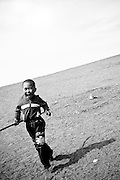 A young boy runs in rural Mongolia.