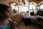 Palestinian women are seen in a bedroom heavly damaged by bullet holes in Beit Lahiya in Gaza July 8,2006. The Israeli army moved back from the houses that they were positioned in .(Photo by Heidi Levine/Sipa Press).